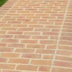 Clay brick pavers with mortar joints set on concrete base