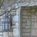 Multi-paned light fixture and stone facade of a Tudor revival